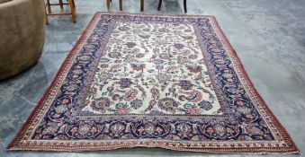 Cream ground Eastern rug, the central field with allover foliate decoration, on a blue ground,