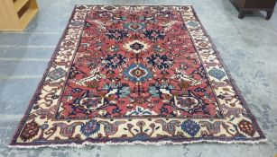 Pink ground rug decorated in blues, creams, browns
