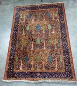 Rust and blue rug featuring stylised pear and other fruiting and flowering trees with a royal blue