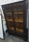 20th century oak display cabinetwith two glazed doors enclosing shelves, turned supports and