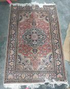 Persian style rug with salmon field, with palmette arabesque and spandrels surrounded by floral