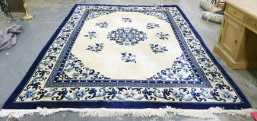 Blue and cream large Chinese washed wool rug with central motif of flowers surrounded by other