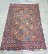 Caucasian-style rug with brown border and two rows of four elephant foot guls surrounded by three
