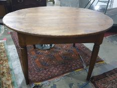 Circular farmhouse-style plank top table raised upon four tapering supports, diameter 135cm approx