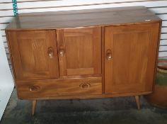 Light elm Ercol sideboardwith two cupboard doors above single drawer with full length cupboard door
