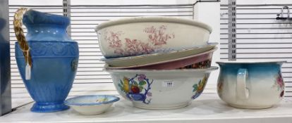 Four assorted ceramic wash basins, a chamber pot, a small dish and a blue and gilt glazed ewer by