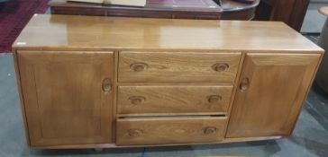 Light elm Ercol sideboardwith three central drawers flanked by cupboard doors, the whole raised