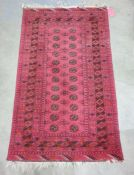 Red Bokhara-style rug with central rectangular field with octagonal patterns surrounded by three