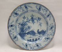 Antique delft-style ceramic platepainted in underglaze blue in the Chinese manner with cockerels