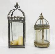 Two garden lanterns for candles, one with glass domed top and cylindical body, one square