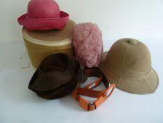 A Pith helmet, cardboard hat box , three hats and an orange leather belt.
