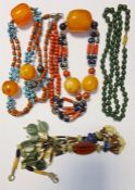 Two bead necklaces, each having large amber-coloured beads amongst others, green hardstone bead