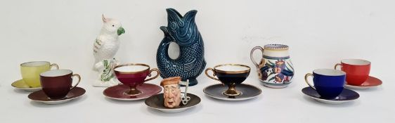 Poole pottery cup, a Dartmouth pottery blue glazed fish guggle jug, a miniature toby jug, part