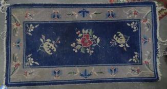 Pair of Chinese blue ground carpets, foliate decoration, 132cm x 75cm (2)