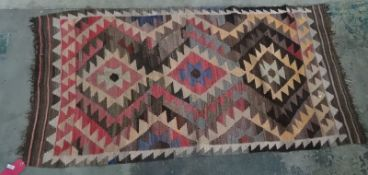 Eastern carpetwith three diamond-shaped lozenges, in pinks, blues, greys and peaches, 188cm x 95.
