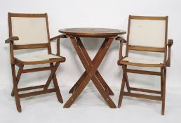 Teak folding garden table and a pair of teak and plastic backed and seated folding chairs, with a