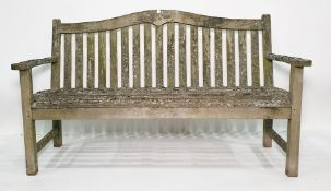 Very weathered garden bench, slat seats and curved back rail