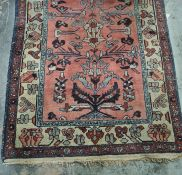 Persian rug, salmon ground decorated in blues, creams and reds, stepped border, 178cm x 104cm