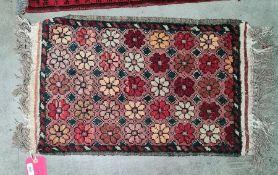 Small Eastern rug, salmon ground, flowerhead motif, 76cm x 41cm