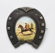Late Victorian silver brooch in the form of a horseshoe, the centre enamel decorated with horse