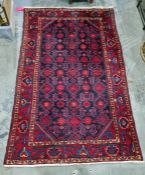 Eastern rug, blue ground with red hooked motifs, canted corners to the central field, wide margin