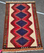Eastern rug, with five blue ground diamond shaped medallions, in pinks, blues, cream and green,