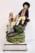 Early 19th century Staffordshire pearlware group of milkmaid and companion, on grassy mound base and