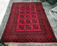 Red ground Persian rug, the central field with 18 elephant's foot guls, on a multi-stepped border,