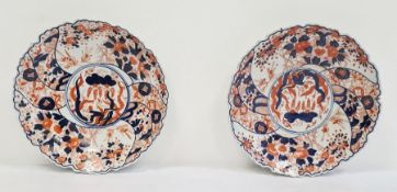 Pair of Japanese Imari circular dishes, each painted with scrolling foliage, bamboo and rockwork,