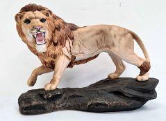 Beswick tinted bisque porcelain model lionon rockwork, 30cm wide
