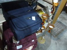 Two suitcases, assorted textilesand a floor-standing candle holder
