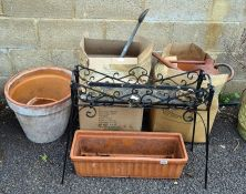 A quantity of terracotta pots, watering cans and pot stand