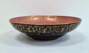 Royal Worcester porcelain shallow bowl, matt black glazed with gilt foliate border to exterior,