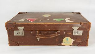Vintage leather suitcase bearing luggage labels
