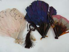 A purple feather and tortoiseshell fan, 19cm, a tortoiseshell and pink/grey feather fan, a wooden