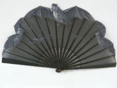 An early 20th century wooden and painted fan, the black organza hand painted with flying bats, the
