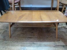 Ercol elm coffee table, rounded rectangular with rail under shelf, on turned tapering supports,