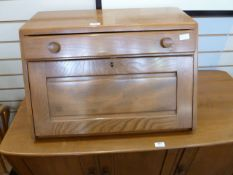 Ercol elm table top bureau with fall-front, single drawer above with circular handles, curved bar