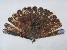A 19th century tortoiseshell brise fan, plain guards and sticks curved edges, with gilt coloured