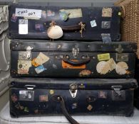 Three large travelling suitcases bearing many travel labels, including British Airport, The