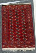 Red ground Eastern Bokhara style rug with thirty elephant foot gulls, 170 x 105cm