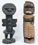 Carved African figure, possibly West African, standing with arms raised and another carved female