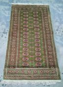 Green ground Persian rug with 28 elephant foot guls arranged across two rows, on a stepped border,