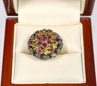 Silver-gilt and ruby cluster ring set seven stones in flowerhead pattern to centre, with surround of