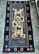 Eastern style rug with cream ground and blue borders, decorated stylised deer, birds and other