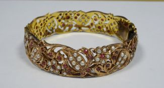 Indian(?) gold ?, ruby and seedpearl bangle, pierced scroll and floral decoration, unmarked, 42.5g