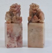 Pair of Chinese carved hardstone modelsof dogs of fo, on square bases, 6.5cm high (2)