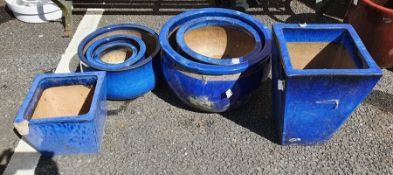 Seven royal blue glazed planters of square tapered and bulbous round forms, largest 51cm diameter (