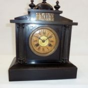 A 20th Century ebonised wooden mantel clock, with frieze decorated with figures, Roman numeral dial,