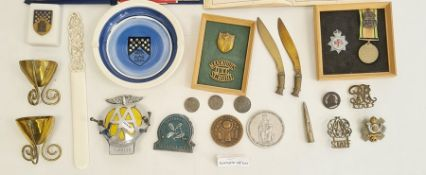 Collection of military badges, a military-style pocket compass, brass trench art, an AA car